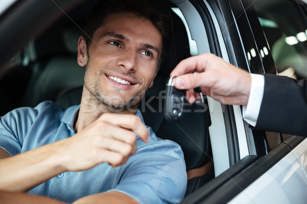 Smiling happy man sitting in his new car Stock photo © deandrobot