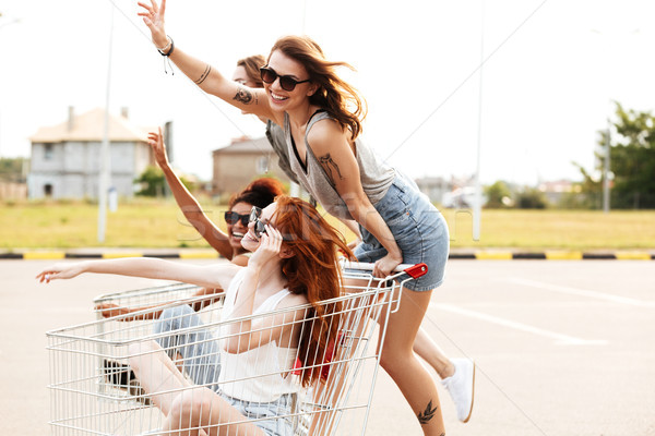 Four happy smiling girls in sunglasses having fun Stock photo © deandrobot
