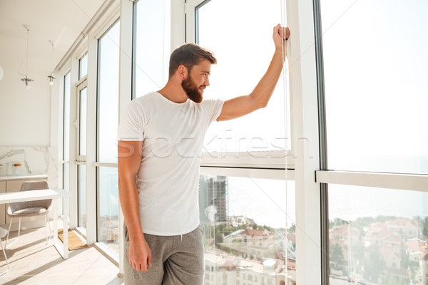 Side view of happy bearded man looking at the window at home Stock photo © deandrobot