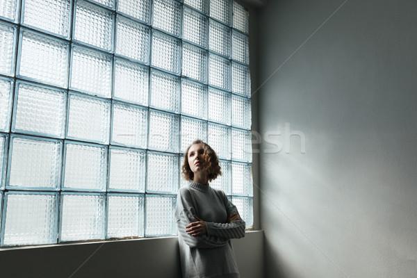 Jonge vrouw permanente venster gevouwen handen Stockfoto © deandrobot