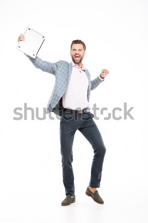Happy young man standing isolated Stock photo © deandrobot
