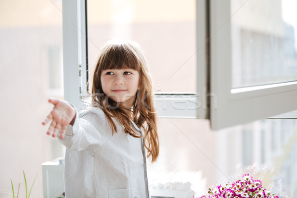 Little girl reaching out hand near window Stock photo © deandrobot