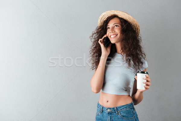 Smiling curly woman in hat drinking coffee Stock photo © deandrobot