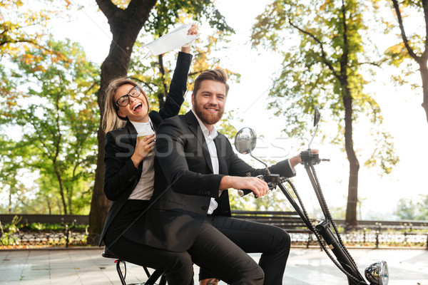 Side view of laughing elegant couple rides on modern motorbike Stock photo © deandrobot