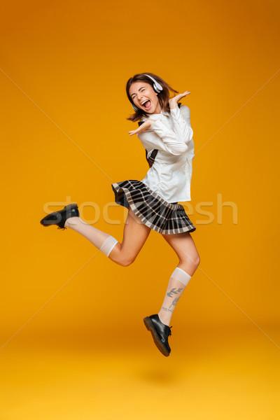 Full length portrait of an excited teenage schoolgirl in uniform Stock photo © deandrobot