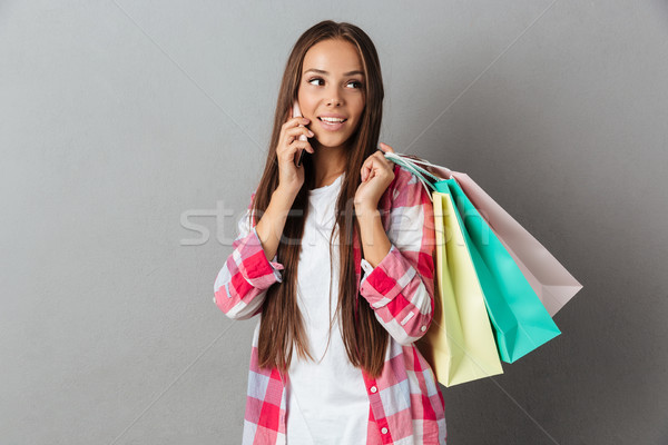 Young pretty woman in casual wear, talking by mobile phone, hold Stock photo © deandrobot