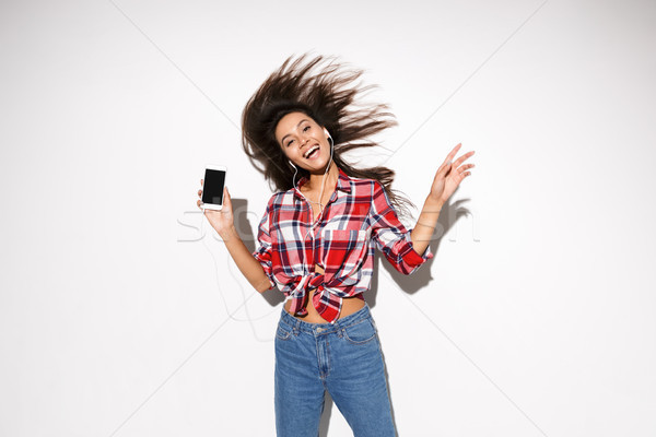 Emotional photo of happy young brunette woman jumping while list Stock photo © deandrobot