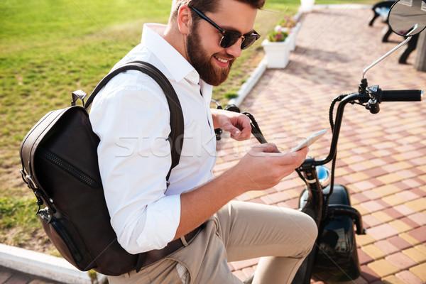 вид сбоку улыбаясь бородатый человека Солнцезащитные очки сидят Сток-фото © deandrobot