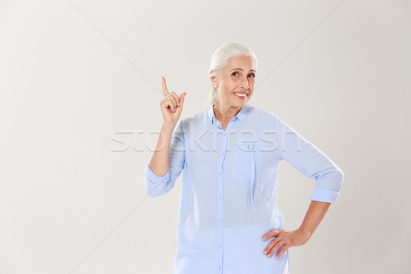 Cheerful gray-haired old lady in blue shirt, pointing with finge Stock photo © deandrobot