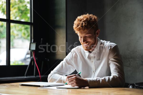 Photo jeunes souriant barbu homme prendre des notes Photo stock © deandrobot