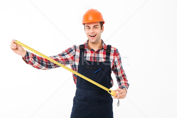 Portrait of a happy young male builder showing Stock photo © deandrobot