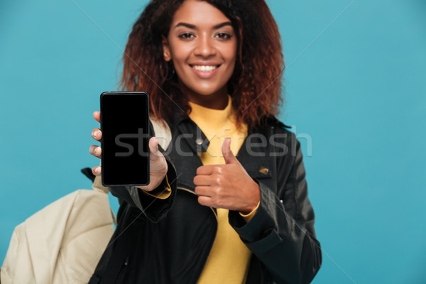 Cheerful african woman student showing display of mobile phone Stock photo © deandrobot