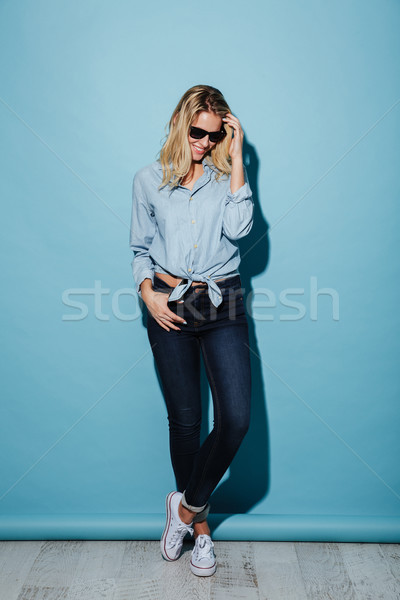 Full length image of pleased woman in shirt and sunglasses Stock photo © deandrobot