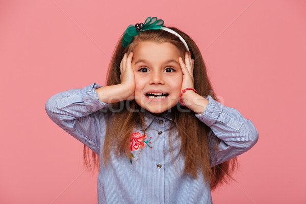 Cheerful little girl reacting emotionally grabbing head with bot Stock photo © deandrobot