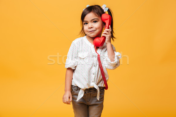 Stock photo: Happy excited little girl talking by red retro telephone.