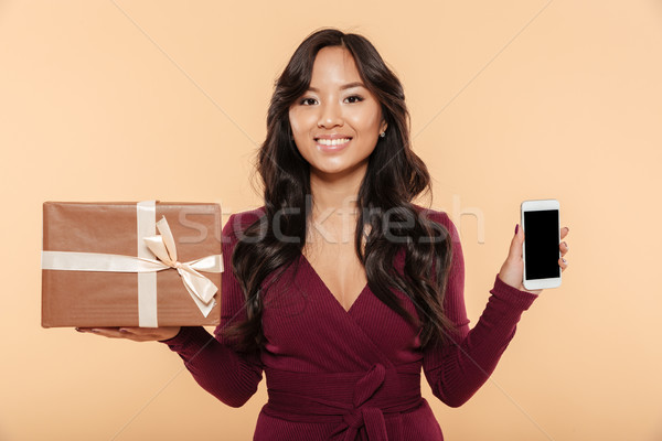 Asian smiling woman in maroon dress demonstrating present box wi Stock photo © deandrobot