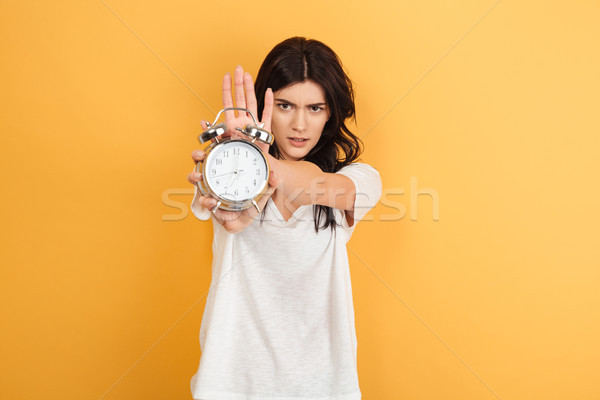 Serious woman isolated holding alarm clock looking camera. Stock photo © deandrobot
