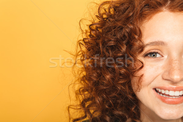 Half face close up of a smiling curly redhead woman Stock photo © deandrobot