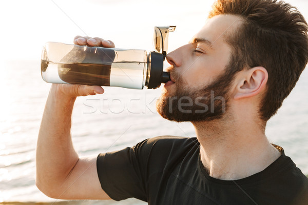 Close up of a thirsty young sportsman drinking water Stock photo © deandrobot