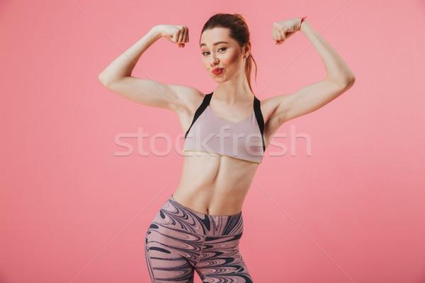 Zadowolony sportsmenka stwarzające biceps patrząc Zdjęcia stock © deandrobot