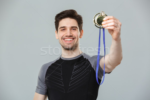 Emotional happy young sportsman holding medal award. Stock photo © deandrobot