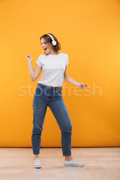 Emotional funny young woman listening music singing. Stock photo © deandrobot