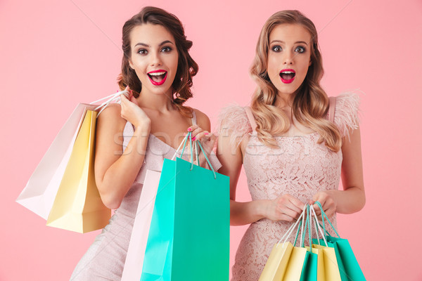 Two Happy elegant women in dresses holding packages Stock photo © deandrobot