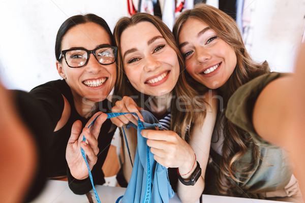 Three smiling young women clothes designers Stock photo © deandrobot