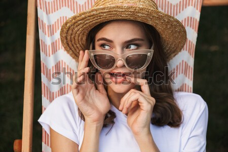 Pretty young girl in sunglasses resting on a hammock Stock photo © deandrobot