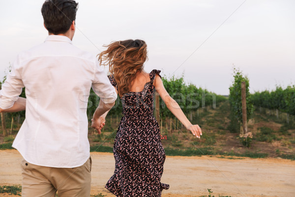 Photo from back of young caucasian couple man and woman walking  Stock photo © deandrobot
