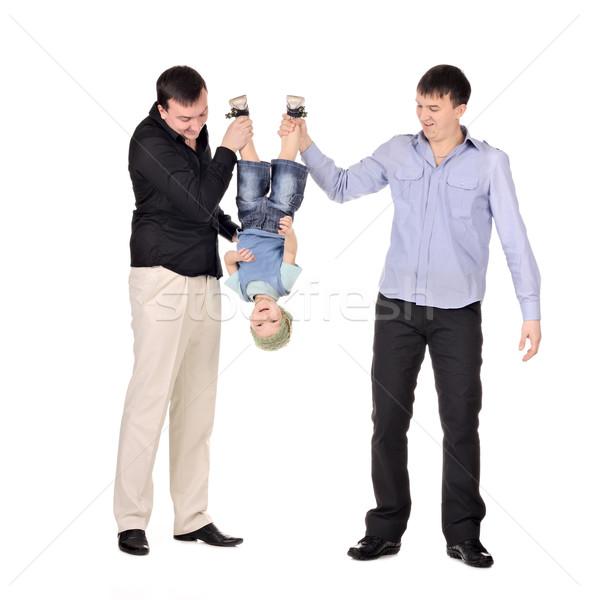Two gusd holding little boy upside down Stock photo © DedMorozz