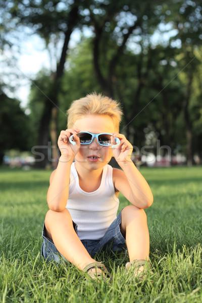 мало мальчика сидят парка глядя Солнцезащитные очки Сток-фото © DedMorozz