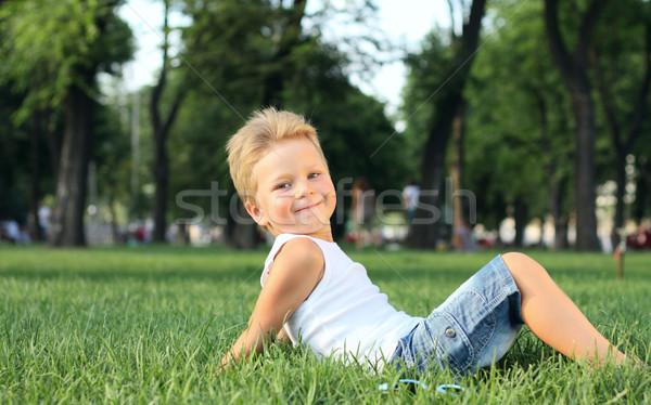 мало мальчика сидят парка трава улыбка Сток-фото © DedMorozz