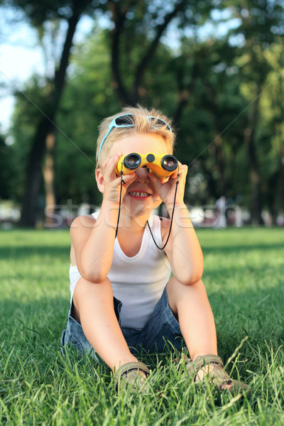 Little boy sitting in the park with a binoculars Stock photo © DedMorozz