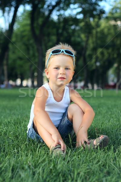 Little boy sitting in the park Stock photo © DedMorozz