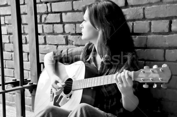 Genç kadın oynama gitar oturma tuğla duvar Stok fotoğraf © dehooks