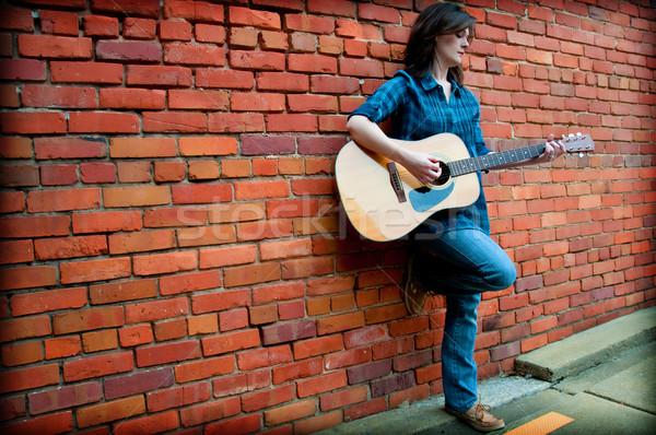 Barna hajú női játszik gitár fiatal áll Stock fotó © dehooks