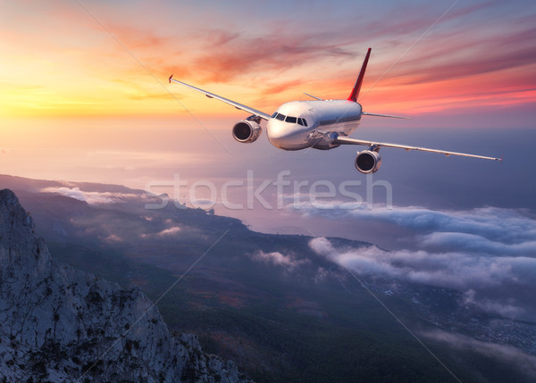 Airplane is flying over low clouds at sunset Stock photo © denbelitsky