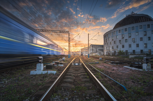 Stock photo: High speed passenger train in motion on railroad track at sunset