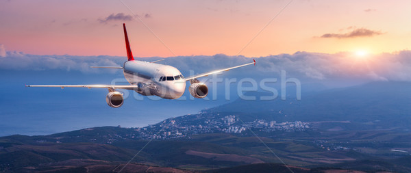 Landscape with white airplane is flying in the orange sky Stock photo © denbelitsky