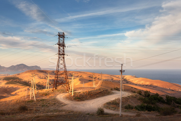 High voltage tower in mountains at sunset. Electricity pylon system Stock photo © denbelitsky