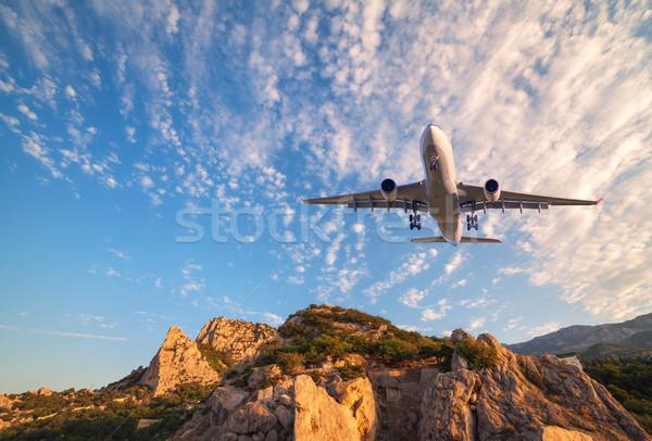 Big white airplane is flying over rocks at sunrise Stock photo © denbelitsky