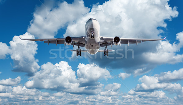White passenger airplane is flying in the blue sky with clouds Stock photo © denbelitsky