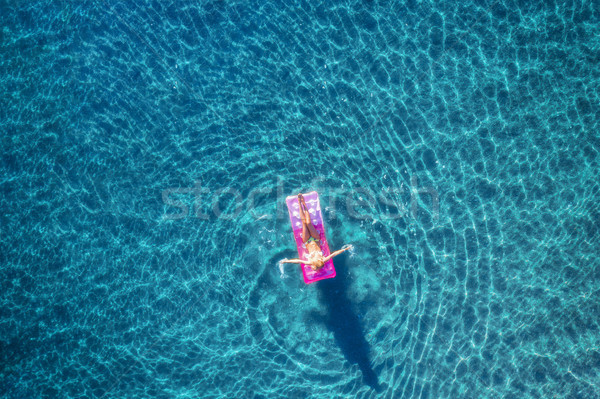 Aerial view of young woman swimming on the pink inflatable mattr Stock photo © denbelitsky