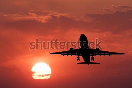 Silhouette atterraggio aeromobili rosso cielo sole Foto d'archivio © denbelitsky