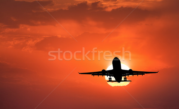 Silhouette of landing aircraft and red sky with sun Stock photo © denbelitsky