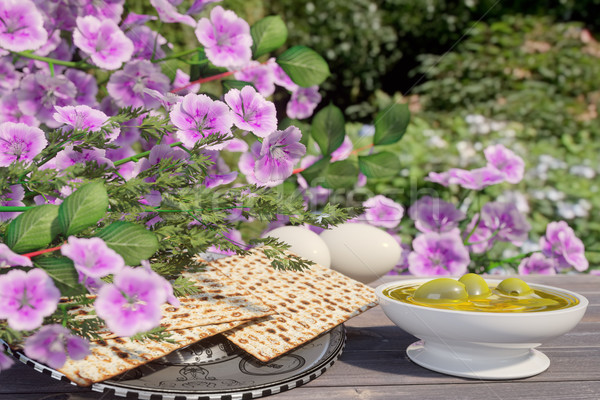 Jewish celebrate pesach passover with eggs,olive, matzo and flowers on nature background Stock photo © denisgo
