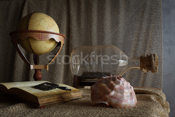 Seashell in interior scene with globe and ship in the bottle concept photo Stock photo © denisgo