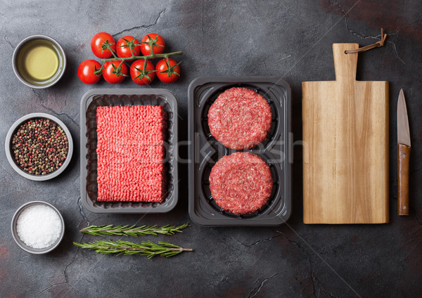 Tray with raw minced homemade beef meat with spices and herbs. Top view. On top of kitchen table bac Stock photo © DenisMArt