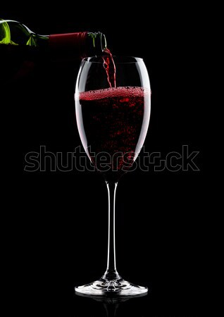 Pouring red wine from bottle to glass on black Stock photo © DenisMArt